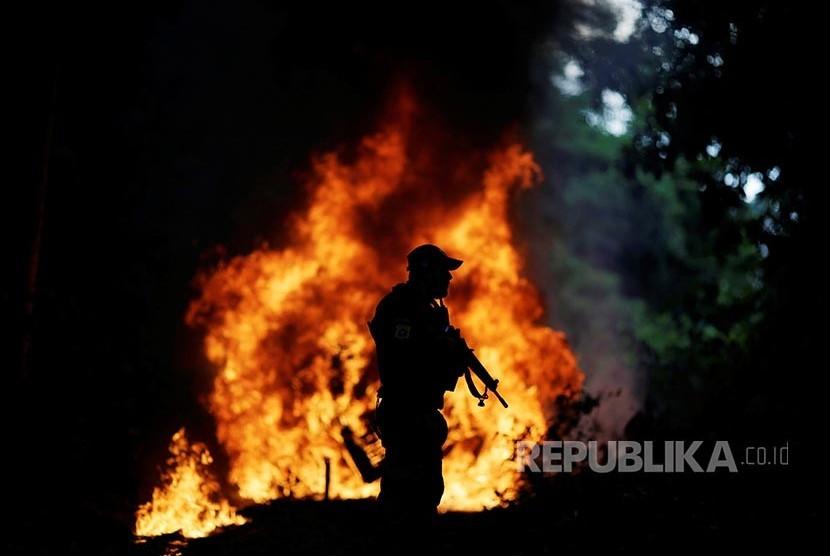 Petugas patroli dengan latar kobaran api yang membakar truk pengangkut kayu milik pelaku ilegal logging di Hutan Amazon Brazil
