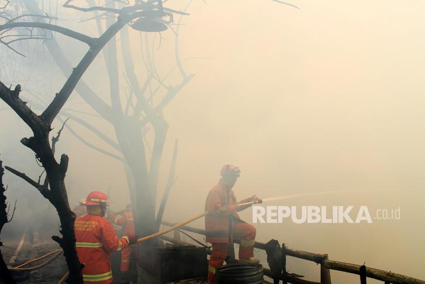 Petugas pemadam kebakaran berusaha memadamkan sisa api saat terjadi kebakaran di kawasan permukiman penduduk, di Cipinang Muara, Jakarta, Senin (21/5).