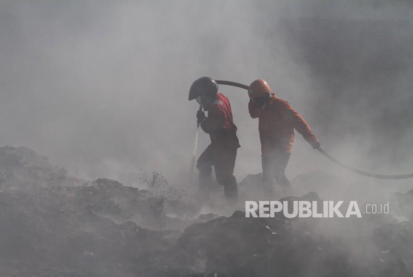 Petugas pemadam kebakaran berusaha memadamkan sisa api saat terjadi kebakaran pabrik pengolahan limbah plastik di Grogol, Sukoharjo, Jawa Tengah, Jumat (23/11/2018).