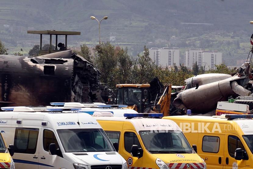 Petugas pemadam kebakaran dan petugas keamanan sipil bekerja di lokasi kecelakaan pesawat militer yang fatal di Boufarik, dekat ibukota Aljazair, Algiers, Rabu (11/4).