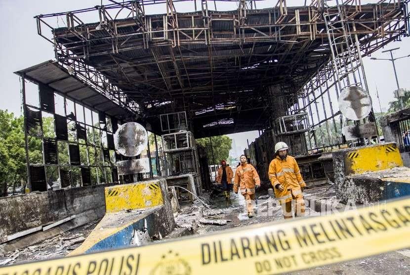 Petugas pemadam kebakaran memeriksa bangunan yang terbakar usai dipadamkan di Gardu Tol Pejompongan, Jakarta, Kamis (27/9).