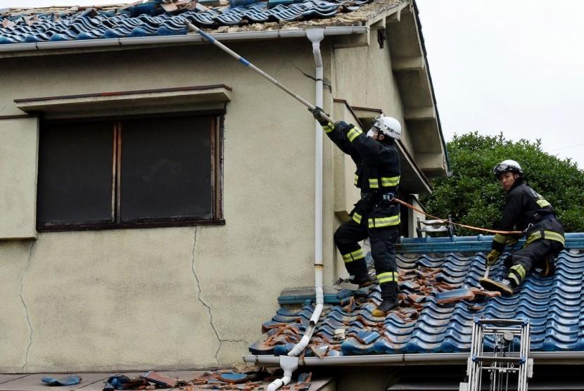 Petugas pemadam kebakaran mencoba menghilangkan puing-puing di atap rumah yang rusak, setelah gempa berkekuatan 6,1 di Osaka, bagian barat Jepang, Senin (18/6) oagi. Gempa bumi ini menewaskan tiga orang dan lebih dari 50 orang terluka.