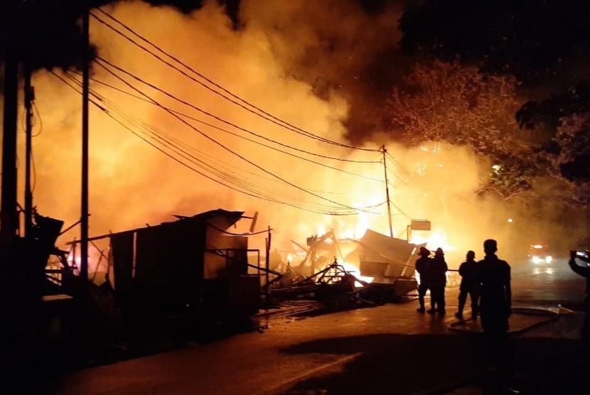 Petugas pemadam kebakaran sedang berjibaku memadamkan api yang membakar belasan lapak pedagang dan rumah semi permanen di samping Kantor Pos Kota Bekasi, Jalan Lapangan Multiguna, Bekasi Timur, Kamis (18/7) pukul 08.30 WIB. Hingga kini api masih terus berkobar.
