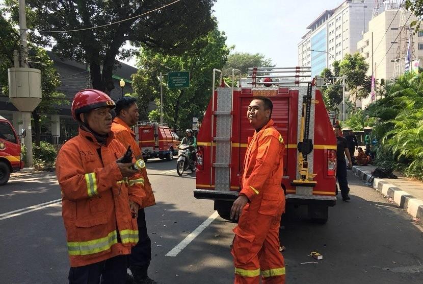 Petugas pemadan kebakaran usai menjinakkan api di Gedung Kementerian Perhubungan di Jakarta, Ahad (8/7).