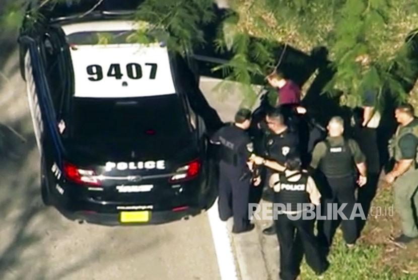 Petugas penegak hukum menangkap seorang pria tak dikenal (dalam warna merah tua), menyusul penembakan di Marjory Stoneman Douglas High School di Parkland, Florida, Rabu (14/2).