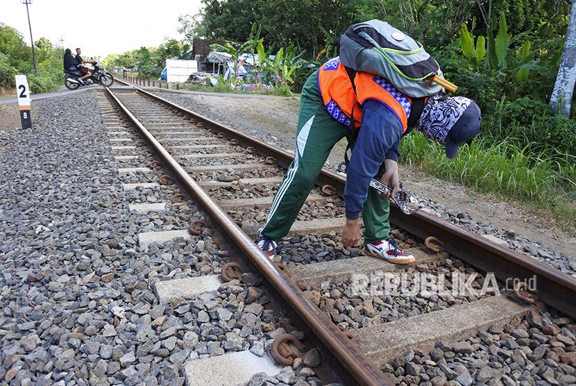 Petugas Penilik Jalan (PPJ) kereta api berjalan memeriksa keamanan rel kereta api di Kelurahan Banjarsari, Glagah, Banyuwangi, Jawa Timur, Selasa (12/6).