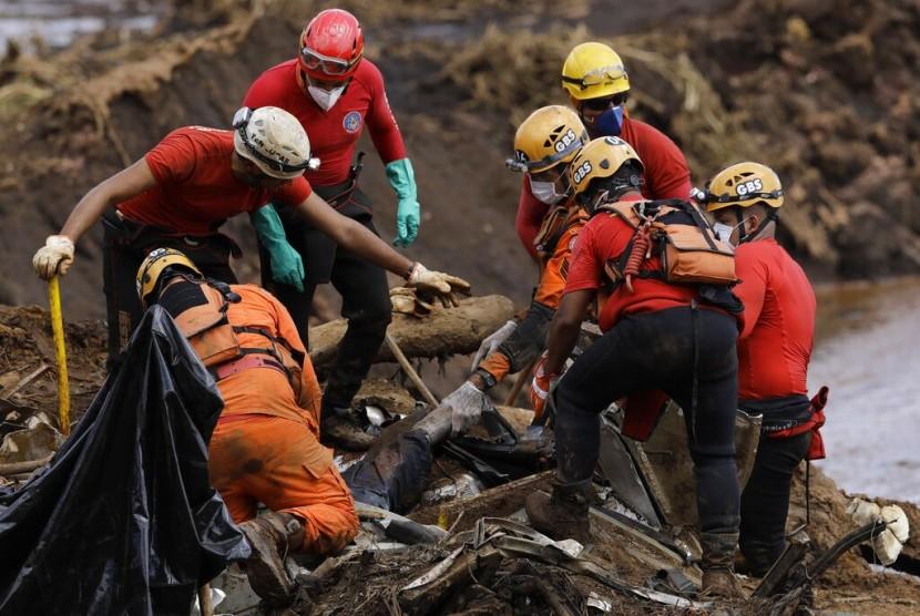 Petugas penyelamat mengevakuasi jasad dari lumpur korban bendungan limbah ambruk milik perusahaan tambang Vale di Brumadinho, Brasil, 28 Januari 2019.