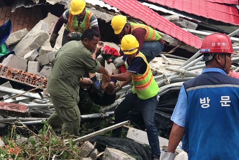 Petugas penyelamat mengevakuasi korban ambruknya gedung di Provinsi Preah Sihanouk, Kamboja, Sabtu (22/6).