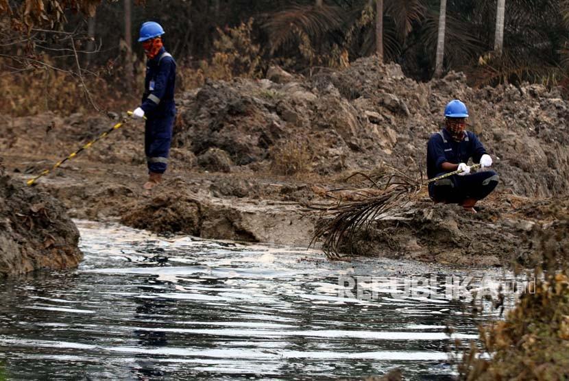 Petugas Pertamina mengawasi saluran pembuangan cairan minyak (Lesser) dari lubang ledakan sumur minyak illegal warga di Desa Pasir Putih, Ranto Panjang Peureulak, Kabupaten Aceh Timur, Kamis (26/4).
