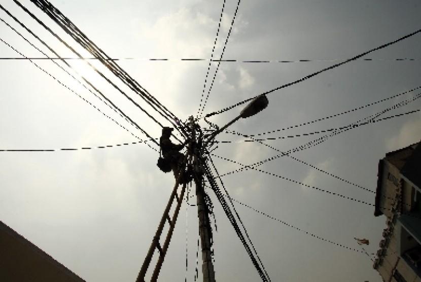 Petugas Perusahaan Listrik Negara memperbaiki instalasi listrik di kawasan Tebet, Jakarta. Pemerintah berencana menaikan TDL 15% sepanjang 2013 dibagi pada empat kuartal.