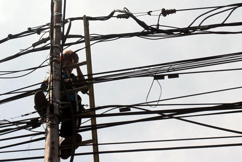 Petugas PLN melakukan perawatan rutin jaringan listrik di Jalan Raya Bogor, Kabupaten Bogor, Jawa Barat, Jumat (22/7).