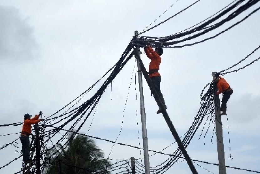 Petugas PLN memeriksa kabel jaringan listrik di kawasan Kota Tua, Jakarta, Selasa (27/1).