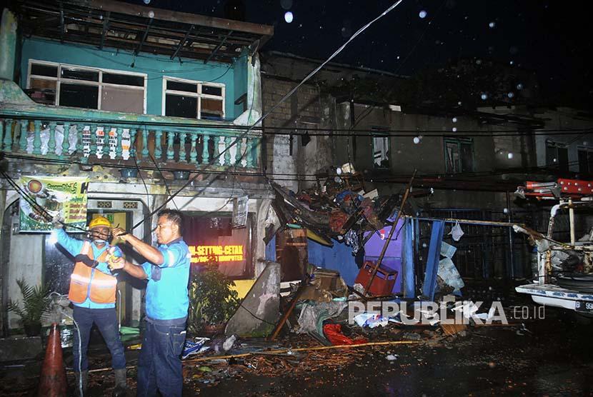 Petugas PLN memperbaiki jaringan listrik yang terputus akibat angin puting beliung di wilayah Batu Tulis, Bogor, Jawa Barat, Kamis (6/12)