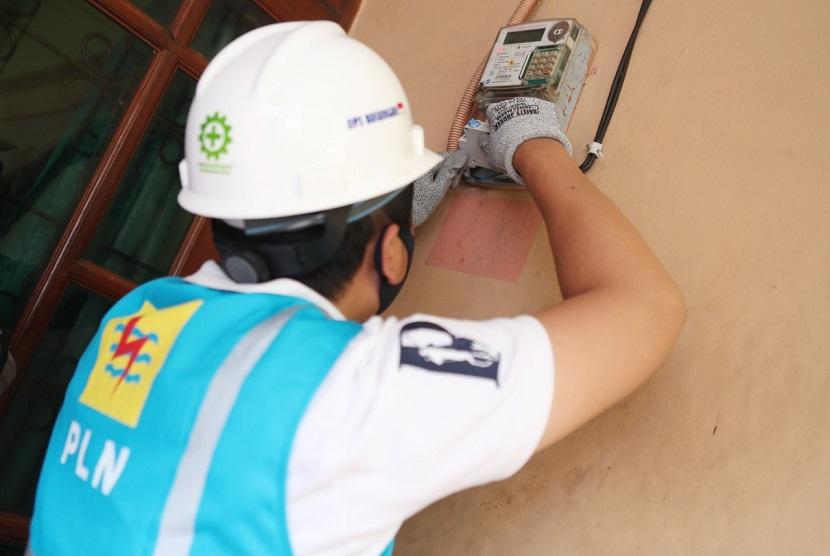 Petugas PLN sedang memeriksa KwH Meter.