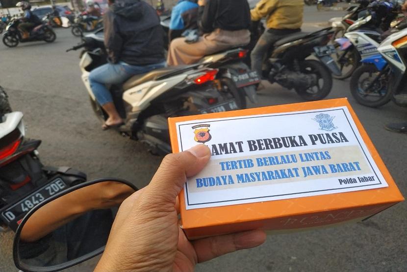 Petugas Polantas Polda Jabar membagikan takjil di simpang Jl Terusan Buah Batu-Sukarno Hatta Bandung, Jumat (17/5).