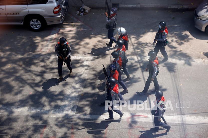 Petugas polisi anti huru hara bergerak untuk membubarkan pengunjuk rasa selama demonstrasi di Yangon, Myanmar, Ahad (7/3)..