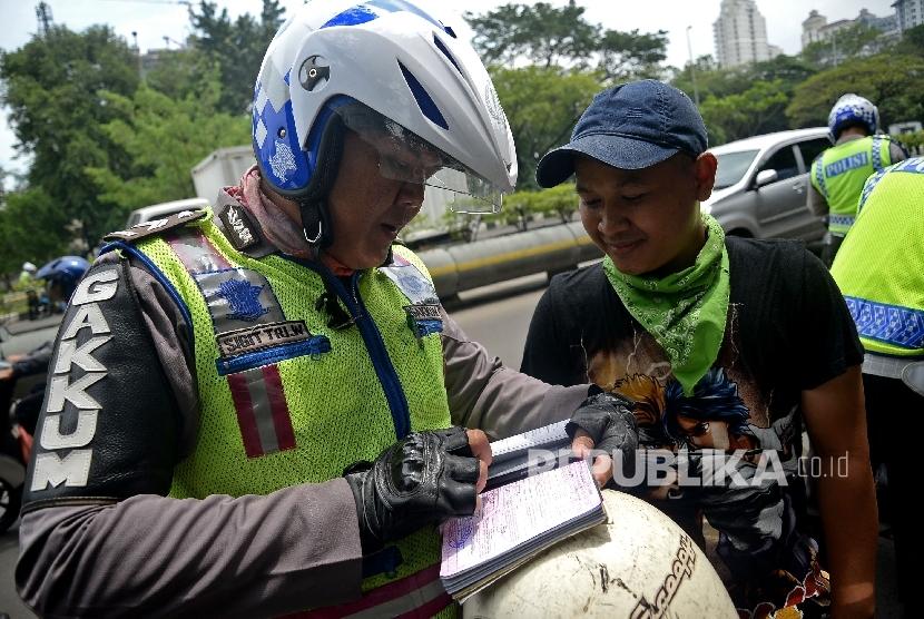 Petugas polisi melakukan penindakan terhadap pelanggar lalu lintas.
