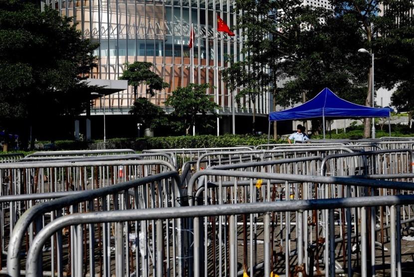 Petugas polisi melihat ke arah penghalang di sekitar gedung dewan di Hong Kong, Jumat (14/6). Suasana kembali tenang di Hong Kong setelah berhari-hari digelar protes oleh aktivis HAM dan mahsiswa menentang UU yang membiarkan tersangka diadili di pengadilan daratan Cina.