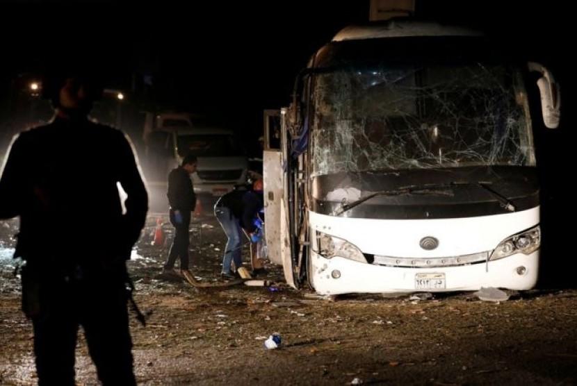 Petugas polisi memeriksa bus yang terkena ledakan bom di dekat Piramida Giza, Kairo, Jumat (28/12)