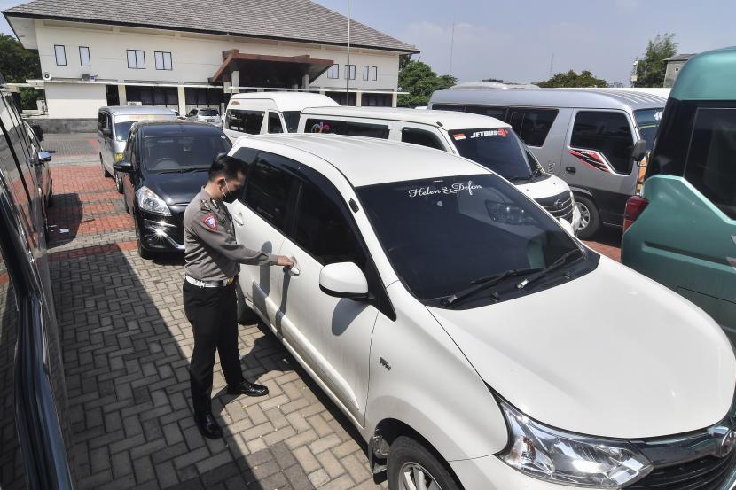 Petugas polisi memeriksa mobil travel atau taksi gelap yang disita di halaman Polres Metro Kabupaten Bekasi, Jawa Barat, Senin (10/5/2021).