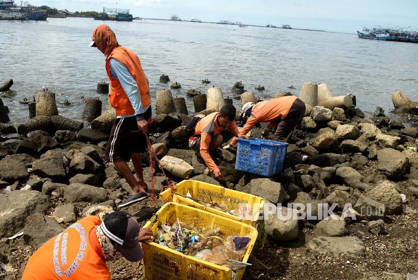Petugas PPSU membersihkan sampah laut di kawasan Kali Adem, Jakarta Utara, Senin (1/1). Pembersihan ini dilakukan secara oleh petugas untuk menjaga kebersihan laut.