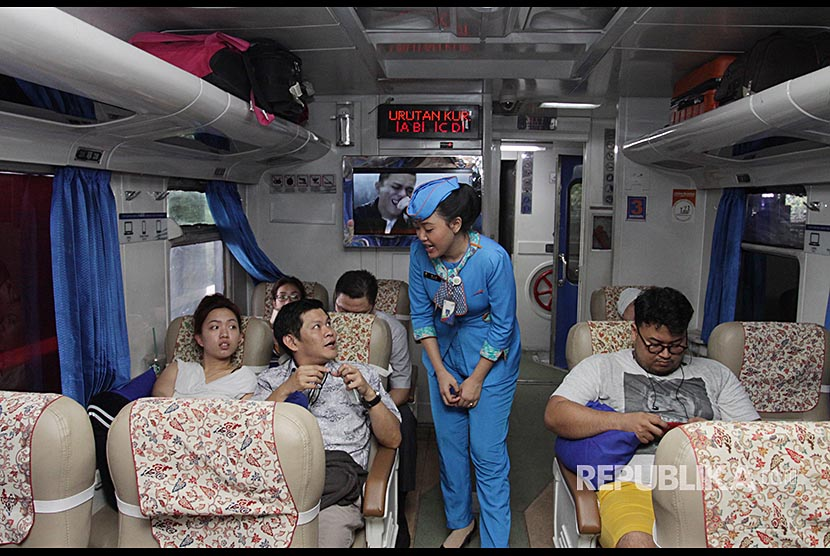 Petugas PT KAI melayani penumpang Kereta Api Arjawinangung Jakarta - Cirebon dalam program kesiapan PT KAI Mudik Lebaran 2018 di Stasiun Gambir, Jakarta, Jumat (18/5). PT KAI menyatakan telah siap 100 persen menghadapi arus mudik 2018.