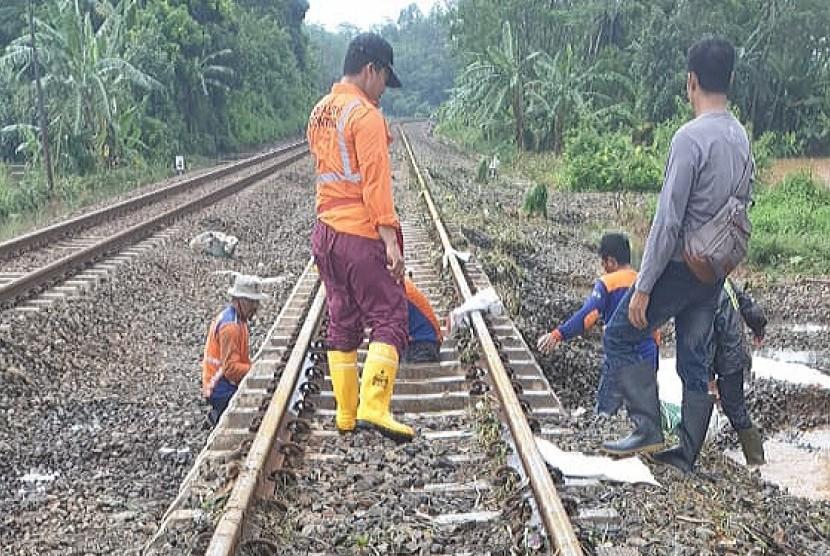 Petugas PT KAI membenahi jalur kereta api setelah terendam banjir di wilayah Ujungnegoro, Kabupaten Batang, Jawa Tengah, Ahad (27/1). Akibat banjir 11 perjalanan kereta sempat terhambat.