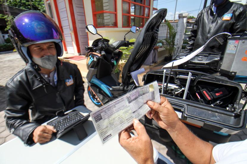 Petugas Samsat melayani pembayaran pajak kendaraan warga melalui fasilitas sepeda motor Sijempol di Desa Panggoi, Lhokseumawe, Aceh, Jumat (24/9/2021). UPTD Badan Pengelolaan Keuangan Aceh wilayah V Lhokseumawe meluncurkan sepeda motor Sijempol atau sistem jemput pajak untuk memudahkan pengurusan pembayaran pajak e-Samsat bagi pengendara roda dan roda empat sebagai upaya meminimalisir penunggakan pajak kendaraan periode 1 Januari -1 September 2021 dimana hanya 35.459 unit kendaraan atau 27 persen yang membayar pajak dari 128.698 unit total kendaraan.