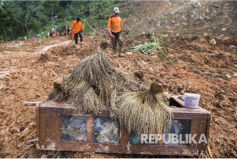 Petugas SAR gabung melintas di dekat tumpukan padi yang terdampak reruntuhan tanah longsor di kampung Cimapag, Desa Sirnaresmi, Kecamatan Cisolok, Kabupaten Sukabumi, Jawa Barat, Jumat (4/1/2019).