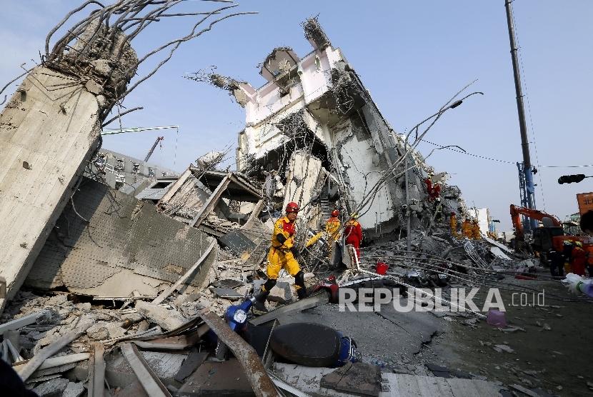 Petugas SAR mencoba mengevakuasi korban dari gedung yang rubuh akibat gempa di Taiwan, Sabtu (6/2).