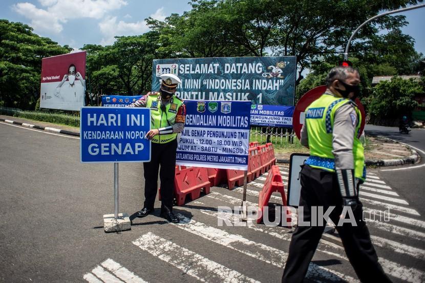 Petugas Satlantas Polres Metro Jakarta Timur bersiap bersiap melakukan pengendalian mobilitas ganjil genap untuk pengunjung TMII di Jalan Pintu 1 TMII, Jakarta Timur, Sabtu (18/9/2021). Direktorat Lalu Lintas (Ditlantas) Polda Metro Jaya memberlakukan kebijakan pembatasan mobilitas warga dengan sistem ganjil genap pada dua kawasan tempat wisata Taman Mini Indonesia Indah (TMII) dan Taman Impian Jaya Ancol pada hari Jumat, Sabtu, dan Minggu mulai pukul 12.00-18.00 WIB.