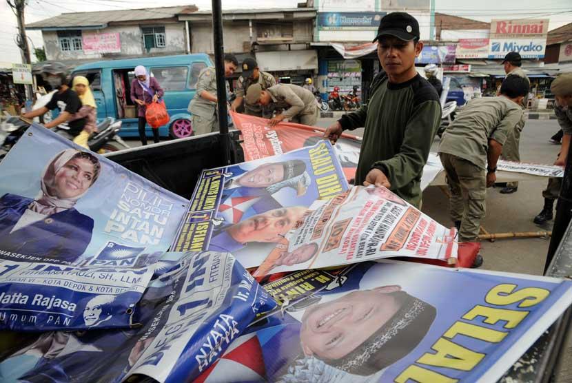 Petugas Satpol PP dan Panwaslu kota Depok menertibkan alat peraga kampanye (APK) sejumlah caleg di sekitar kawasan Depok, Jawa Barat, beberapa waktu lalu.