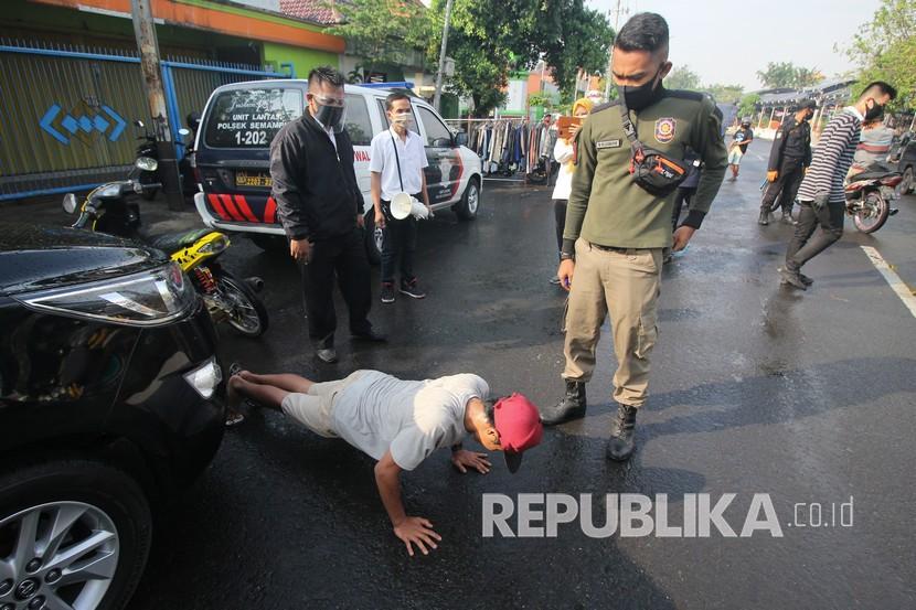 Petugas Satpol PP menghukum warga yang tidak mengenakan masker untuk