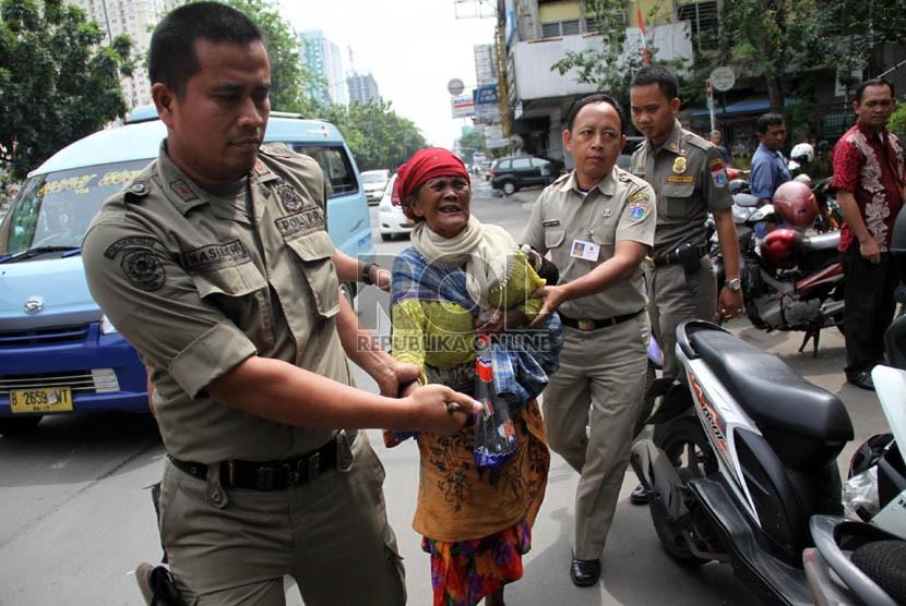 Petugas Satpol PP merazia sejumlah gelandangan di Jalan Hayam Wuruk, Jakarta, Rabu (10/7).  ( Republika/ Yasin Habibi)