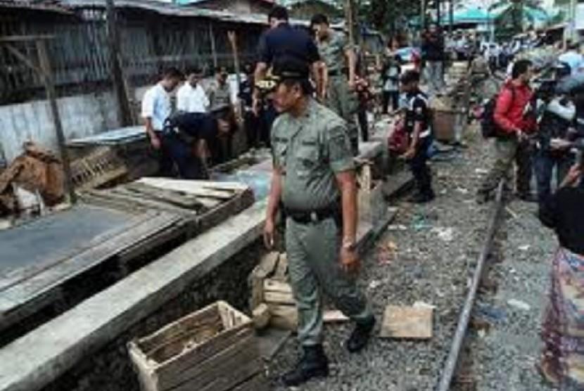 Petugas Satpol PP saat merazia PKL yang berjualan di atas rel kereta.