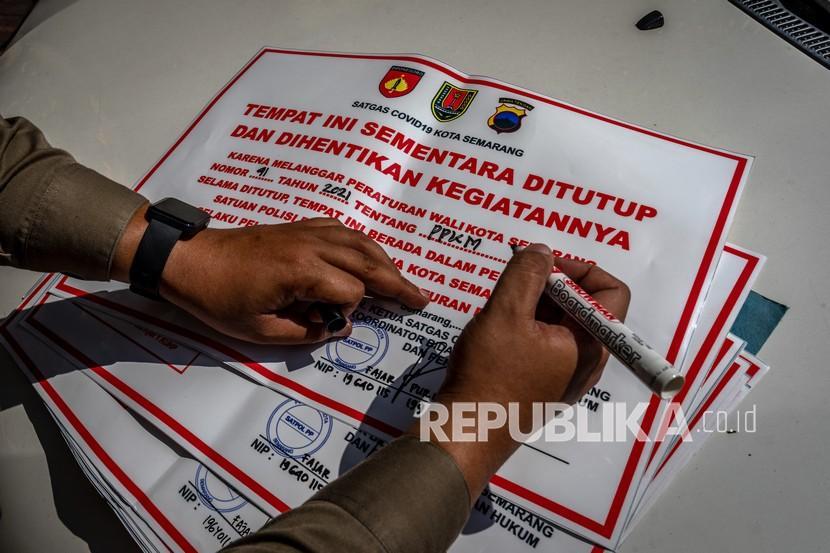 Petugas Satuan Pamong Praja (Satpol PP) menyiapkan lembar segel tempat usaha yang melanggar aturan saat giat penerapan PPKM Darurat