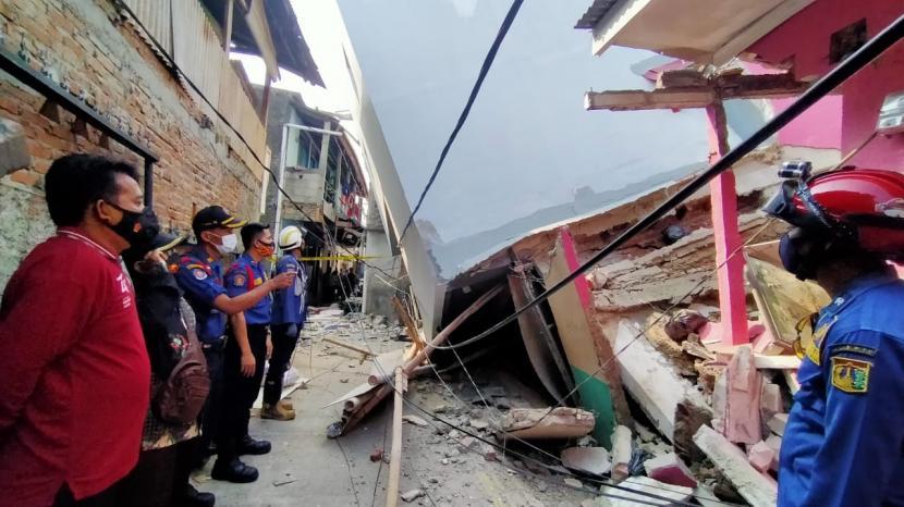 Petugas sedang berada di lokasi  rumah dua lantai yang roboh dan menimpa rumah lainnya di Jalan Turi 3, RT 12 RW 16, Kelurahan Kapuk, Cengkareng, Jakarta Barat, Ahad (16/5).