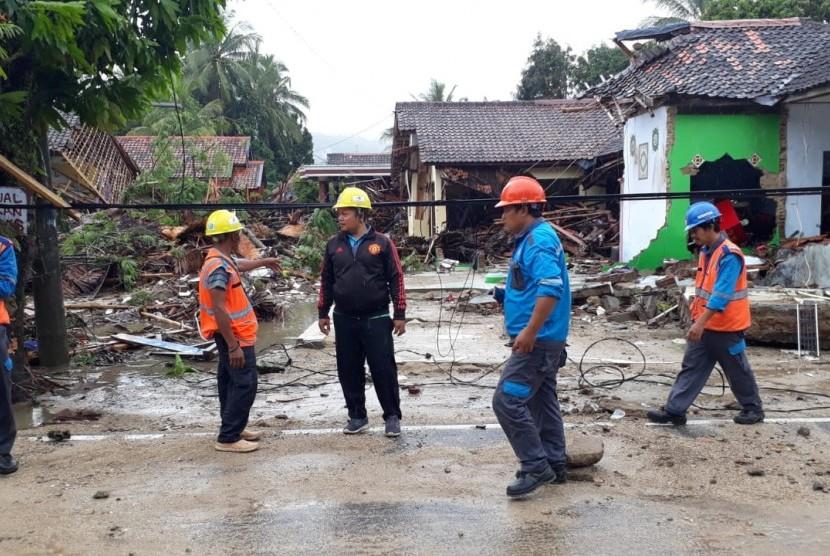Petugas sedang memperbaiki kabel listrik di Anyer yang terkena tsunami, Ahad (23/12).