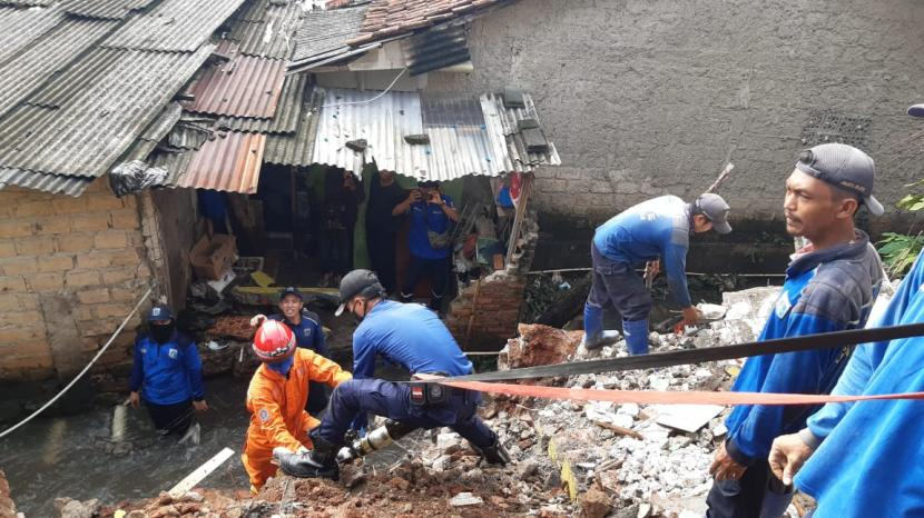 Petugas sedang mengangkat material longsor yang menutup aliran kali di Kelurahan dan Kecamatan Jagakarsa, Jakarta Selatan, Kamis (6/5).