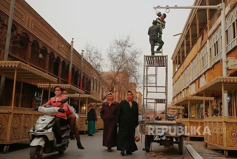 Petugas setempat memasangkan kamera CCTV di sudut  kota tua Khasgar, Daerah Otonomi Xinjiang Uighur, China.