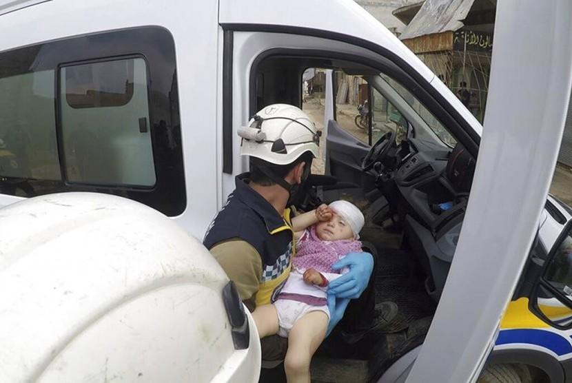 Petugas sipil membawa seorang bayi usai serangan rudal di jalanan Kota Nairab, di barat Idlib, Suriah, Ahad (7/4).