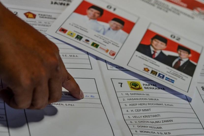 Petugas sortir dan lipat surat suara menunjukan surat suara yang terdapat percikan tinta di surat suara DPR RI, di Gudang Logistik KPU Kota Tasikmalaya, Jawa Barat, Selasa(19/2/2019).