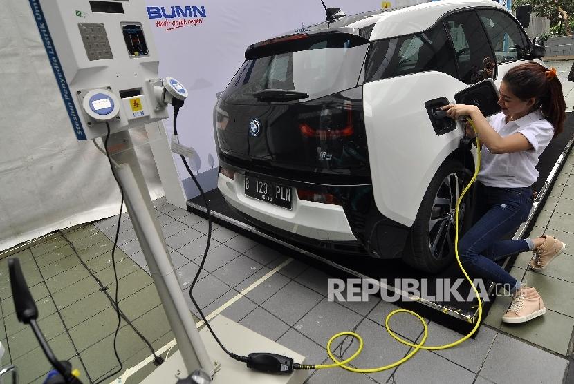 Petugas stan melakukan pengisian kendaraan mobil berbahan bakar listrik disalah satu stan saat acara LIKE (Learning, Innovation, Knowledge & Exhibition) di Kantor Pusat PLN, Jakarta, Selasa (17/10).