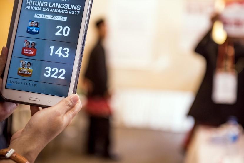 Petugas survei menghitung jumlah suara secara digital saat penghitungan suara Pemilihan Gubernur DKI Jakarta di TPS 28 Cilandak Barat, Jakarta, Rabu (15/2).