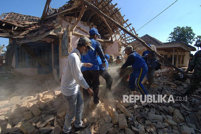 Petugas Tagana dibantu anggota TNI membersihkan puing rumah yang ambruk akibat gempa yang melanda Desa Bula'an, Sumenep, Jawa Timur, Kamis (14/6)