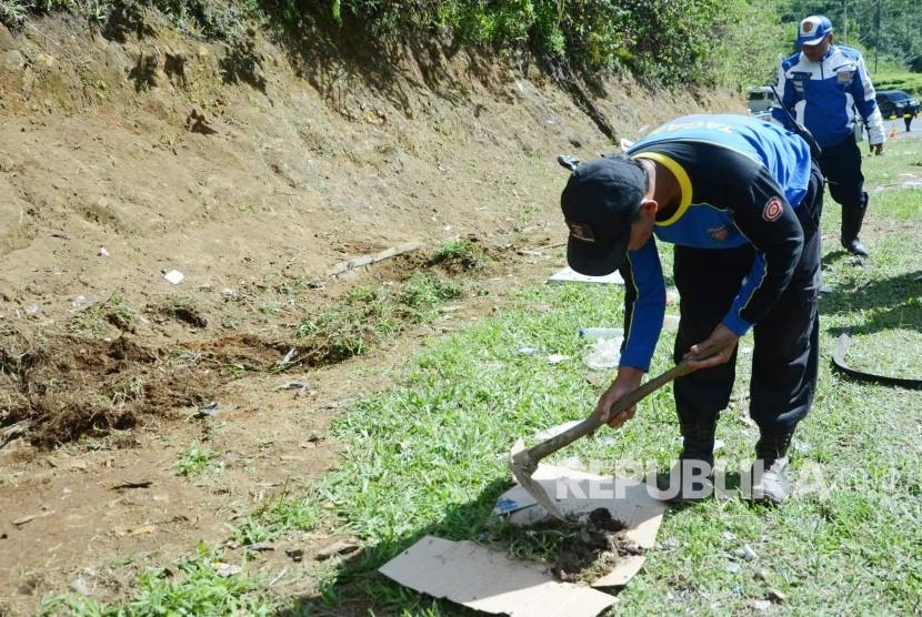 Petugas Tagana mengumpulkan bagian-bagian organ tubuh korban yang masih tertinggal di lokasi kecelakaan bus di Tanjakan Emen, Kecamatan Ciater, Kabupaten Subang, Ahad (11/2).