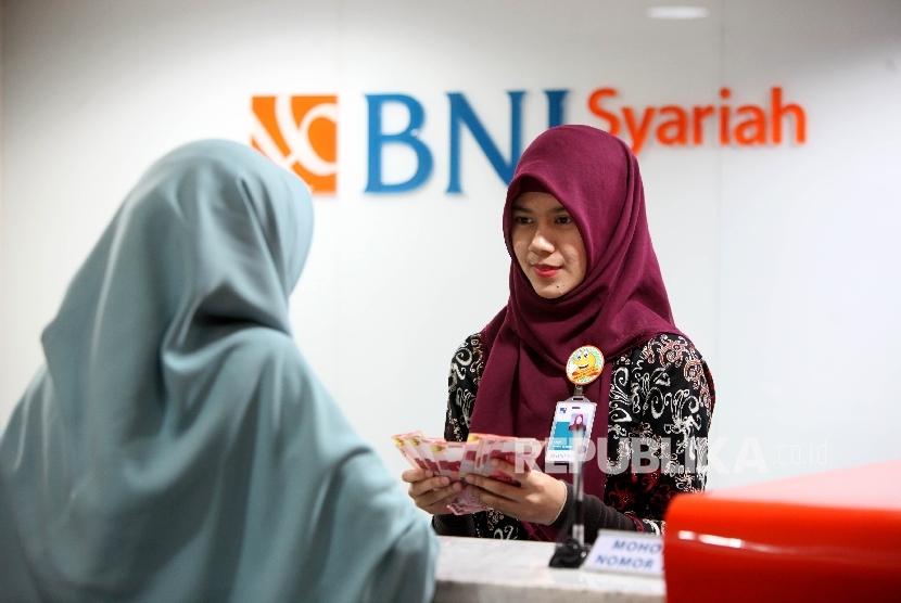 Petugas Teller melayani nasabah di banking Hall BNI Syariah, Jakarta, Jumat (7/7).