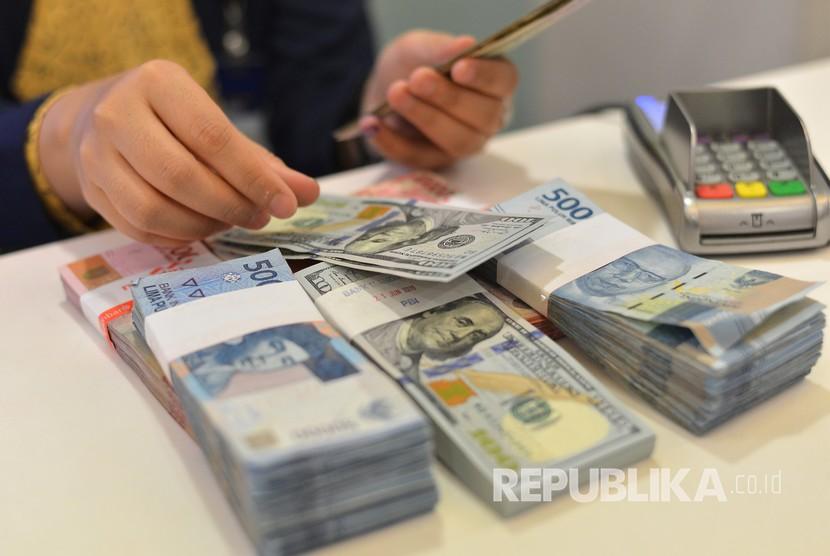 Petugas teller menghitung pecahan uang dolar AS. ilustrasi