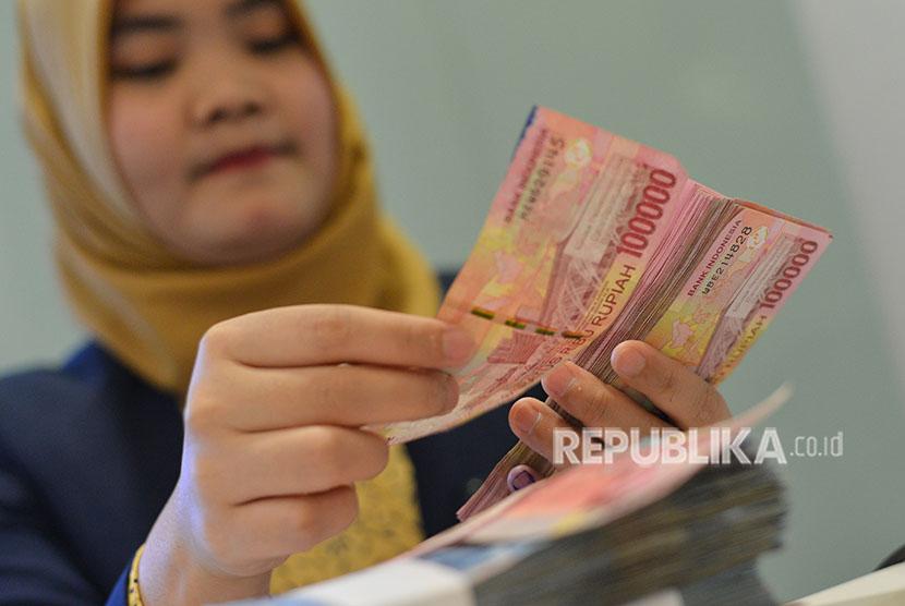 Petugas teller menghitung pecahan uang rupiah di Kantor Pusat Bank Mandiri, Kamis (28/6).