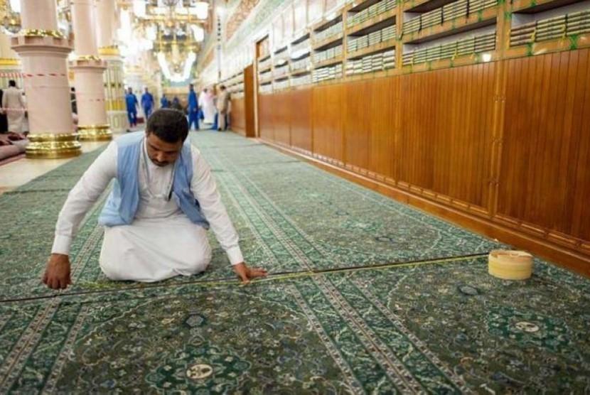 Petugas tengah mengganti karpet di jalur yang menuju ke makam Rasullah SAW dengan karpet biru yang baru.